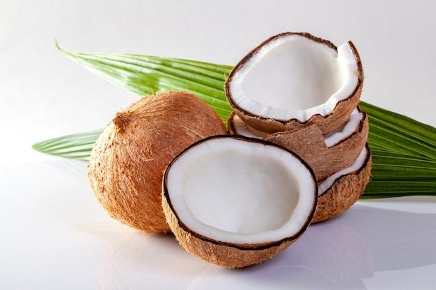 Noix de coco et huile de noix de coco sur fond blanc.