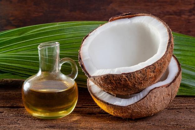 Noix de coco et huile de noix de coco sur fond de bois.