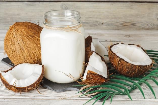 Noix de coco et lait de coco sur table en bois rustique