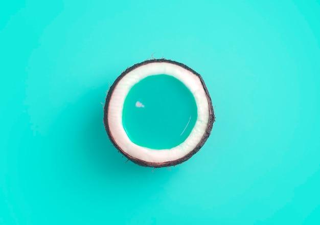 Noix de coco avec liquide de jus de turquoise sur fond turquoise. concept minimal de noix de coco