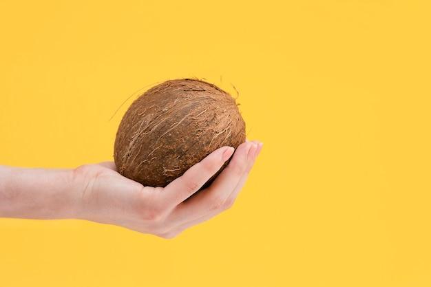 Noix de coco à la main sur fond jaune