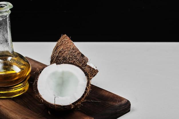 Noix de coco à moitié coupée et bouteille d'huile sur planche de bois.