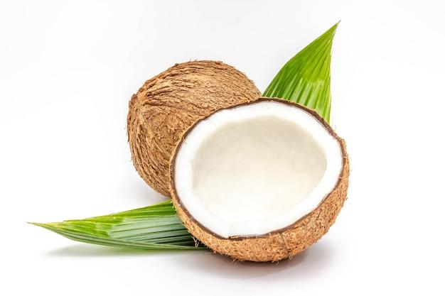 Noix de coco avec moitié et feuilles sur fond blanc