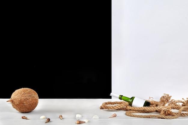 Noix de coco mûre, coquillages, bouteille en verre