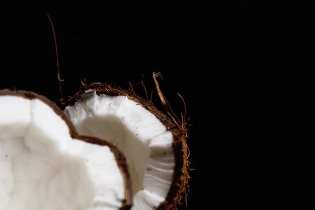 La noix de coco mûre est cassée en deux moitiés isolées sur un fond noir