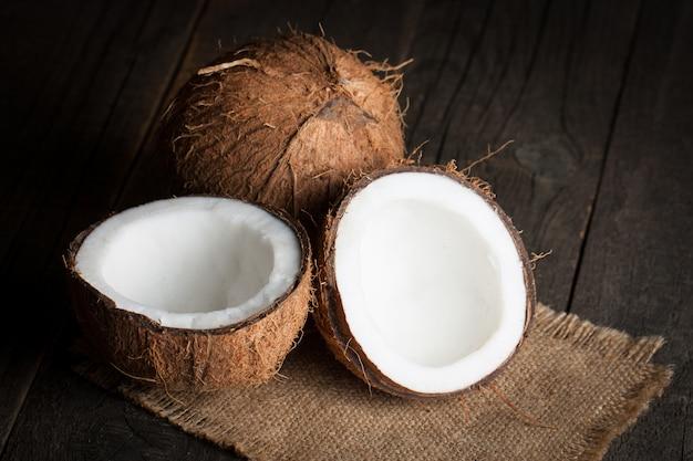 Noix de coco mûres coupées à moitié sur un fond en bois.