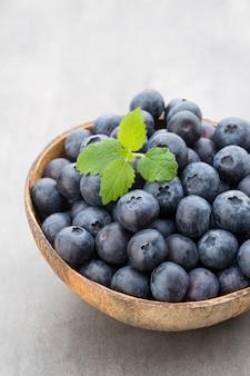 Noix de coco naturelle de bleuets frais dans un bol sur fond gris