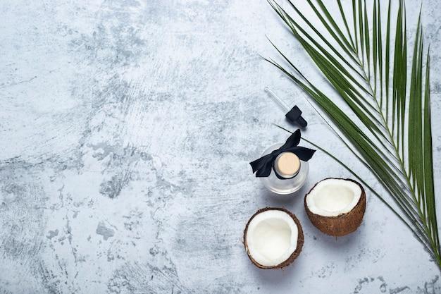 Noix de coco ouverte, bouteille et feuille de palmier sur fond de béton. vue de dessus, mise à plat