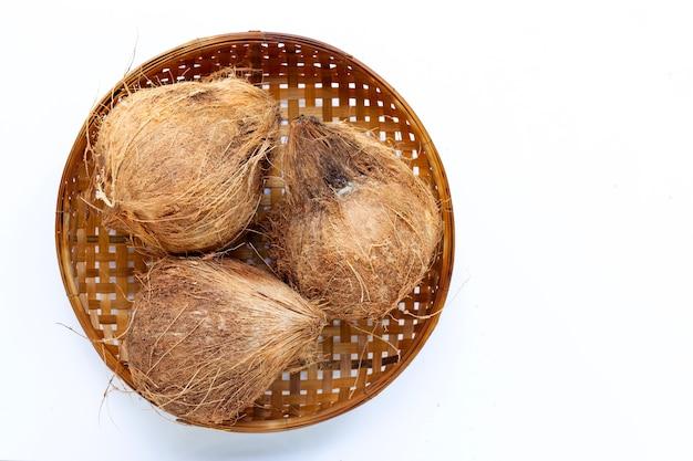 Noix de coco sur panier de battage en bambou en bois sur blanc.