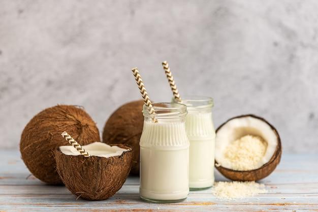 Noix de coco, pot de lait de coco et flocons de coco sur un bois clair.