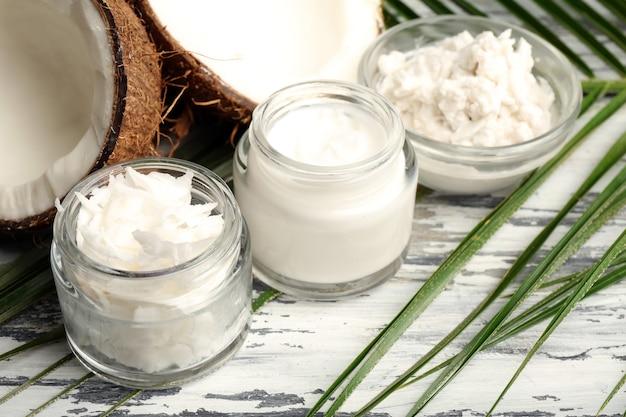 Noix de coco avec des pots d'huile de noix de coco et de crème cosmétique sur table en bois