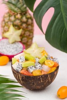 Noix de coco remplie de salade de fruits et feuille de monstera