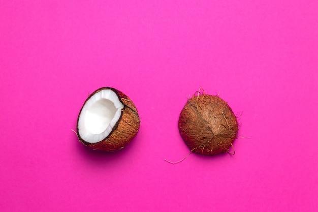 Noix de coco savoureuse en tranches et entière, isolée sur fond rose