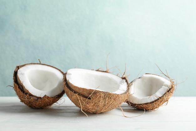 Noix de coco sur table en bois blanc contre gris