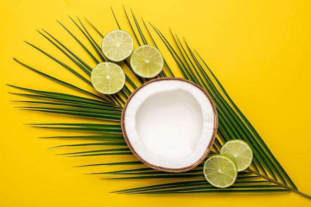 Noix de coco tropicale, palme et citron vert sur fond jaune