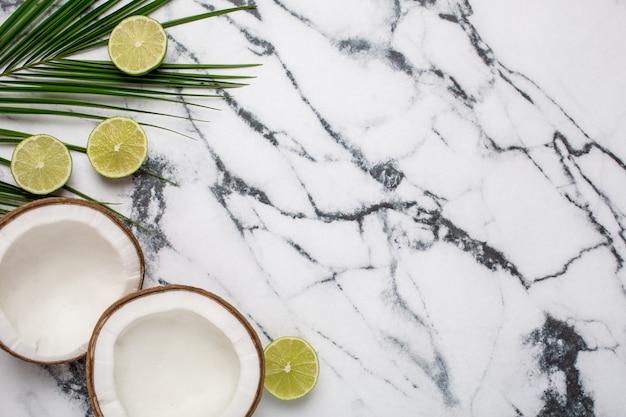Noix de coco tropicale, palme et citron vert sur marbre