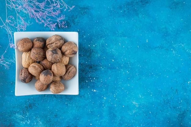 Noix en coque dans un bol , sur la table bleue.