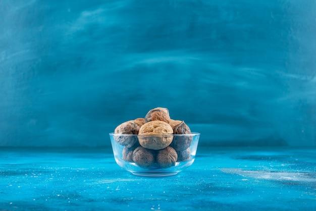 Noix en coque dans un bol en verre , sur la table bleue.