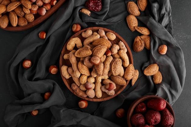 Noix et coquilles d'amande dans une assiette en bois avec des fruits secs autour.