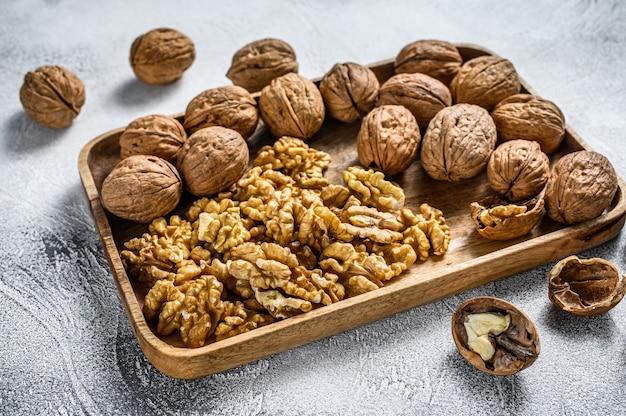 Noix dans une assiette en bois et noyaux de noix