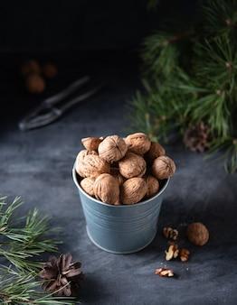 Les noix dans un bocal en métal sur une table en bois parmi l'arbre de noël vert. sombre et maussade