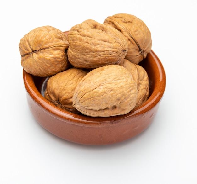 Noix dans un bol d'argile (collection de noix diverses). isolé