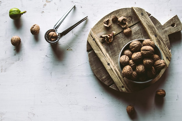 Les noix dans un bol en bois sur la table avec casse-noisette.