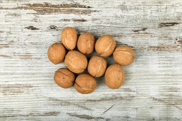 Noix dans les mains. vue rapprochée de noix dans sa paume. les noix sont 4 eau, 15 protéines, 65 lipides et 14 glucides, dont 7 fibres alimentaires. dans une portion de référence de 100 grammes.