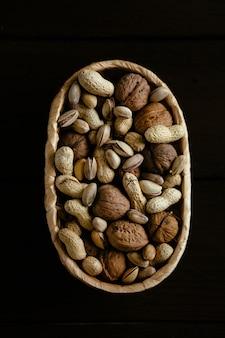Noix dans le panier. noix organiques mélangés dans le panier sur fond noir. groupe de noix différentes