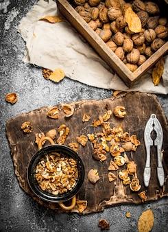Noix décortiquées dans un bol avec casse-noisette sur table rustique.