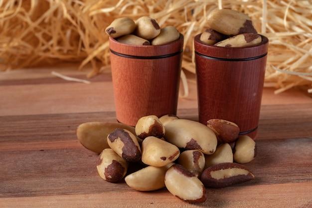 Noix du brésil sur une table en bois et dans une tasse en bois avec fond de paille. (castanha do brasil ou castanha do para)
