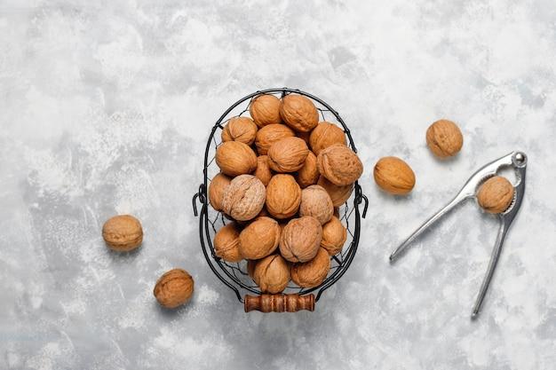 Noix entières en coques dans un panier en métal alimentaire, cerneaux de noix. vue de dessus sur le béton