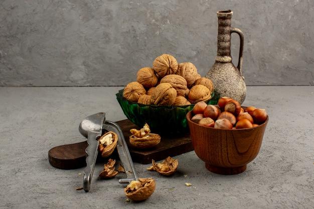 Noix entières noisettes savoureuses à l'intérieur d'un pot brun et d'une assiette verte sur un bureau gris