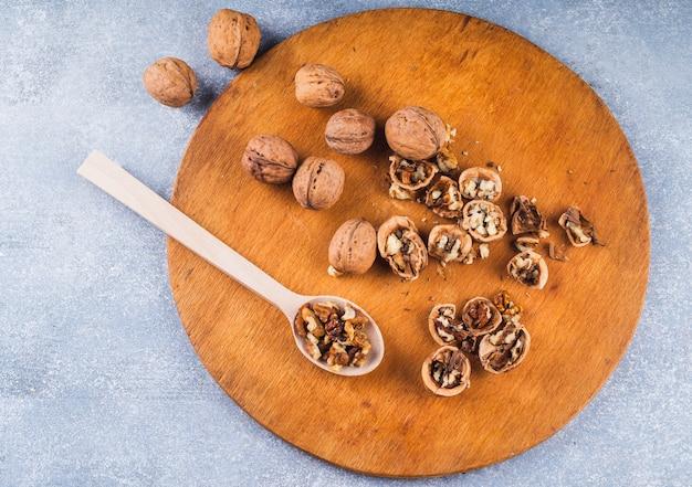 Noix entières et noyau à la cuillère en bois et plateau en toile de fond