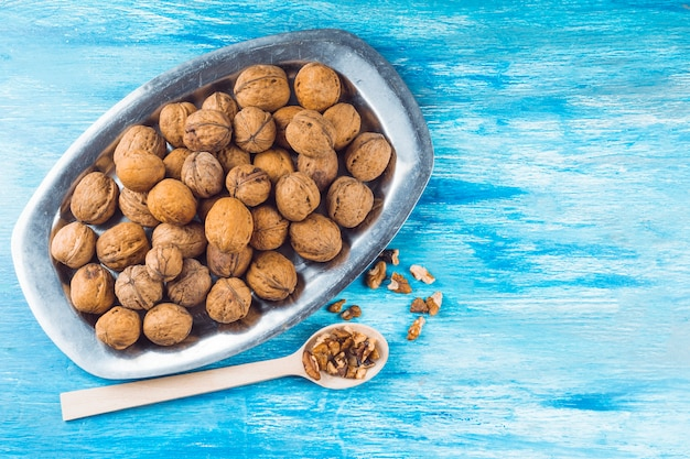 Noix entières sur plateau et noyau de noix sur une cuillère en bois sur fond bleu