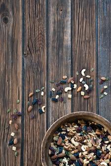 Noix et fruits secs dans un bol en bois sur un fond en bois rustique.