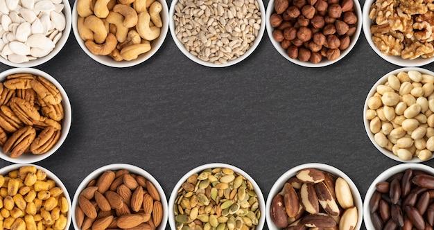 Noix et graines assorties dans des bols sur fond de pierre avec espace de copie.