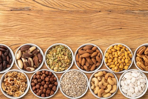 Noix et graines assorties dans des bols sur une table en bois avec espace de copie.
