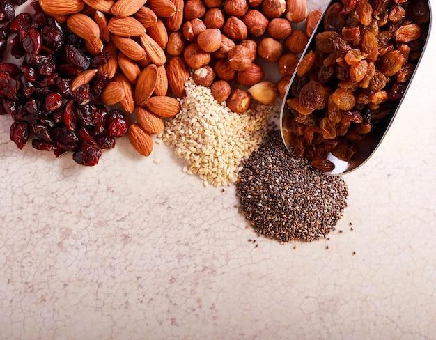 Noix, graines, canneberges et raisins secs sur table en marbre