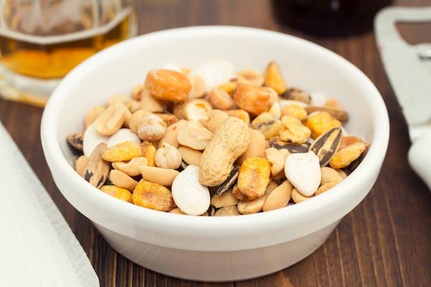 Noix et graines salées sur plat blanc