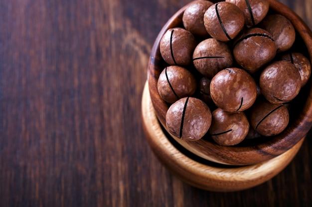 Noix de macadamia en coquillage sur fond en bois. végétarien