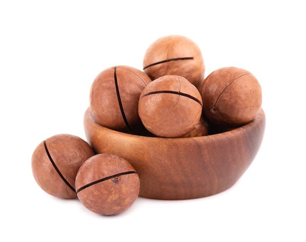 Noix de macadamia dans un bol en bois, isolé. macadamia non décortiquée.