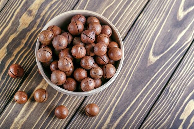 Noix de macadamia dans un bol sur une table en bois avec espace de copie. top wiew.