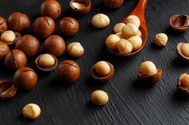 Noix de macadamia décortiquée et noix de macadamia pelée sur un fond texturé noir dans une cuillère en bois