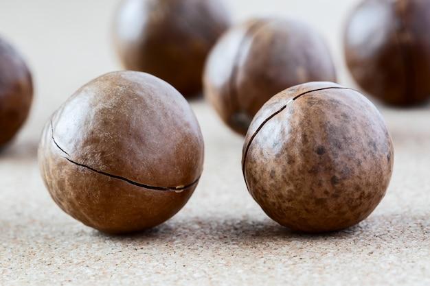 Noix de macadamia entières sur fond marron