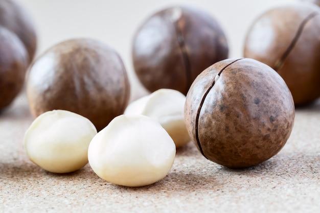 Noix de macadamia entières et noyau sur fond marron