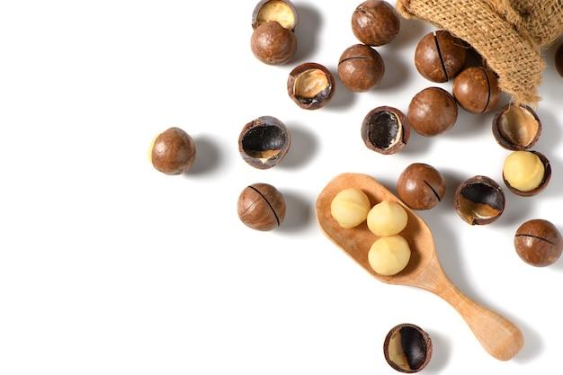 Noix de macadamia pelées dans une cuillère en bois isolé sur fond blanc,