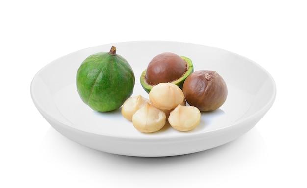 Noix de macadamia en plaque sur fond blanc