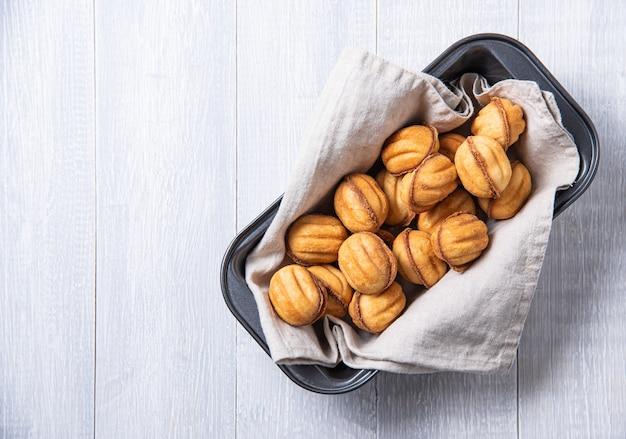 Noix à la main cuites au caramel dans un plat allant au four sur une table blanche. copiez l'espace et la vue de dessus