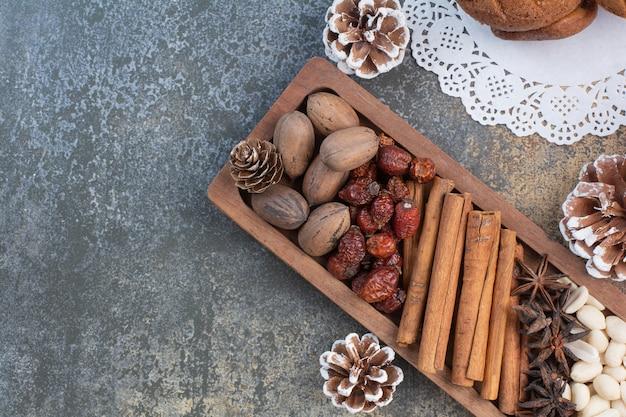 Noix mélangées avec des bâtons de cannelle et des fruits secs sur une plaque en bois. photo de haute qualité